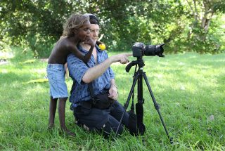 UNICEF/SONY EYE SEE Child Photography workshop faciltated by photographer Giacomo Pirozzi. 15 participants from the indigenous communities. 8/12 April 2013, Milgarri Community Knuckeys Lagoon, Darwin Australia A child stands behind videographer Mark Galer at Bagot community park.